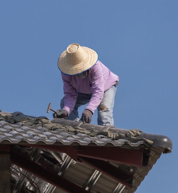 Travailleurs installant des tuiles pour la construction de maisons Photo Premium