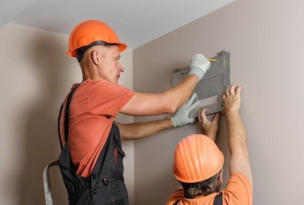 Les Travailleurs Installent Un Système Divisé Pour Un Système De Climatisation Domestique. Photo Premium