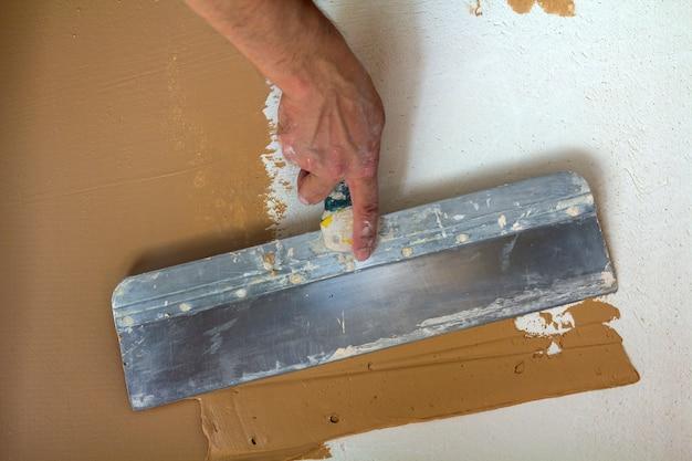 Les Travailleurs De La Rénovation à La Main Plâtrant Le Mur Photo Premium