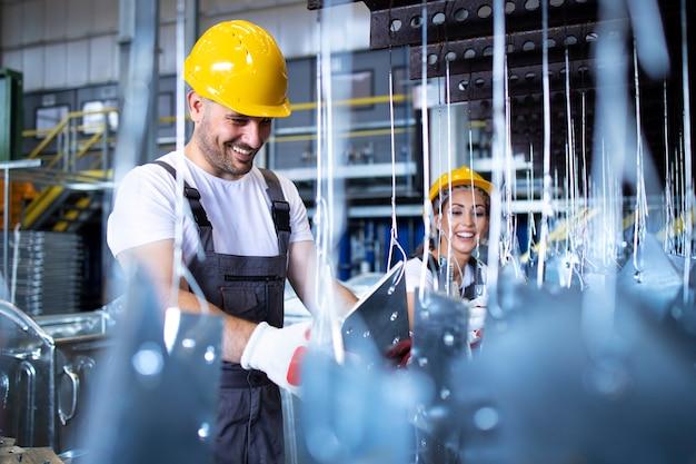 Travailleurs En Uniformes Et Casques De Protection Jaunes Travaillant En Usine Photo gratuit