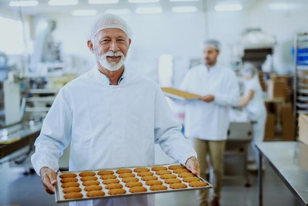 Travailleurs D'usine Alimentaire En Uniformes Stériles Portant Des Plateaux Avec Des Biscuits. Mise Au Point Sélective Sur Le Travailleur Adulte Senior. Photo Premium
