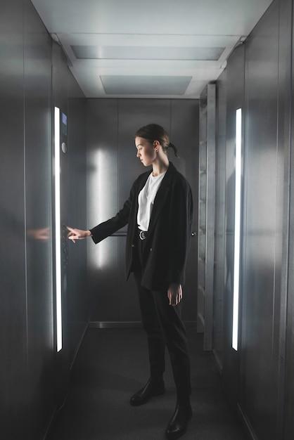 Travailleuse En Appuyant Sur Le Bouton De L'ascenseur. Photo Premium
