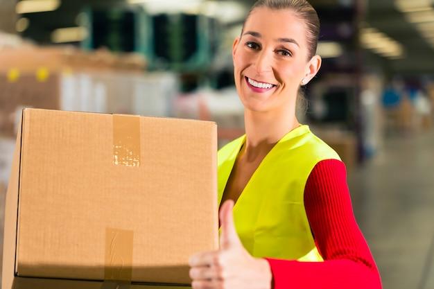 Travailleuse avec gilet de protection détient paquet, debout à l'entrepôt de la société d'expédition Photo Premium