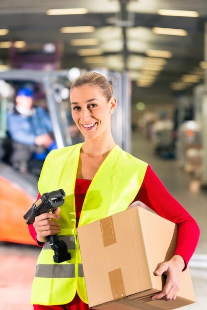 Travailleuse avec gilet de protection et scanner, détient un colis, se tenant devant l'entrepôt de la société de transport, Photo Premium