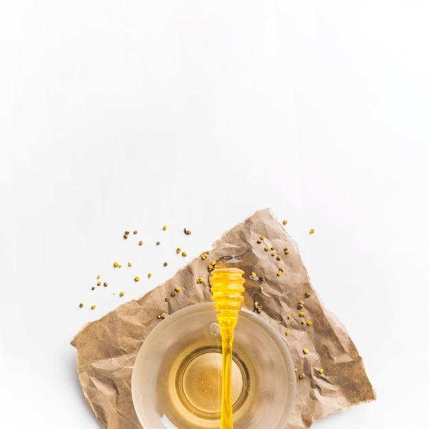 Trempette sur un bol de miel avec des graines de pollen d'abeille sur du papier brun Photo gratuit