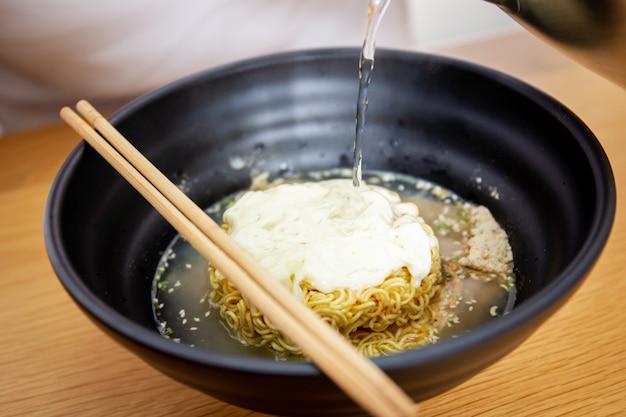 Trempez de l'eau bouillante dans les nouilles au fromage instantanées. Photo Premium