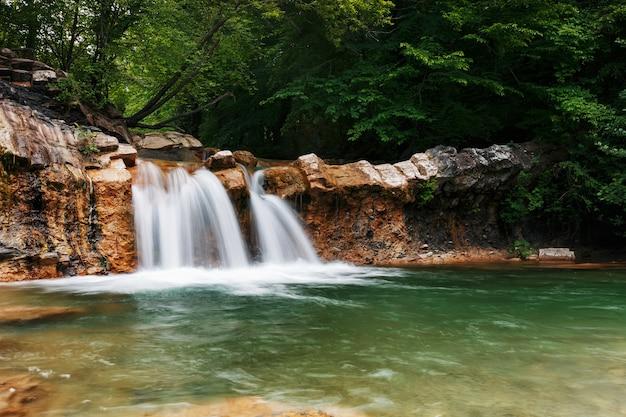 Très belle cascade printanière dans la vallée de la rivière jean dans la forêt Photo Premium