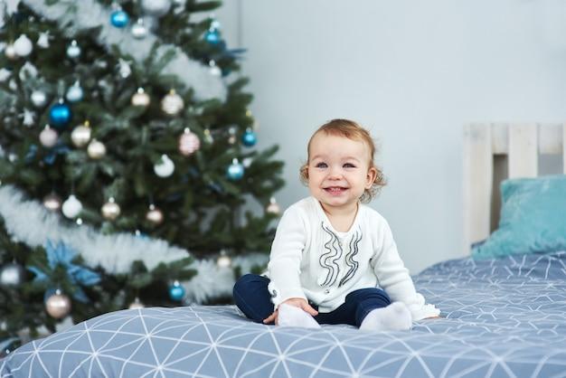 Très belle charmante petite fille blonde en blanc assise sur le lit et regardant la photo sur le fond des arbres de noël souriants à l'intérieur lumineux de la maison Photo Premium