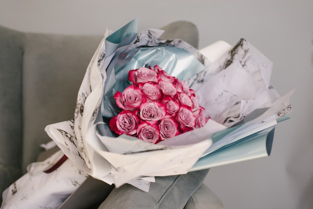 Très belle femme fleuriste tenant un beau bouquet de fleurs colorées sur un fond de mur gris. Photo Premium
