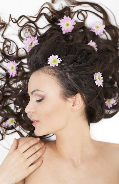 Très Belle Fille Allongée Avec Des Fleurs Aux Cheveux Brillants Dans Ses Cheveux Maquillage Lumineux Isolé Sur Blanc Photo gratuit