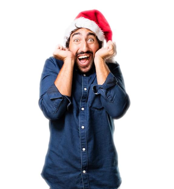 Très heureux avec les poings soulevé l'homme et le chapeau de santa Photo gratuit
