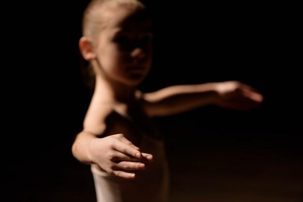 Très jeune ballerine posant sur un fond noir Photo Premium