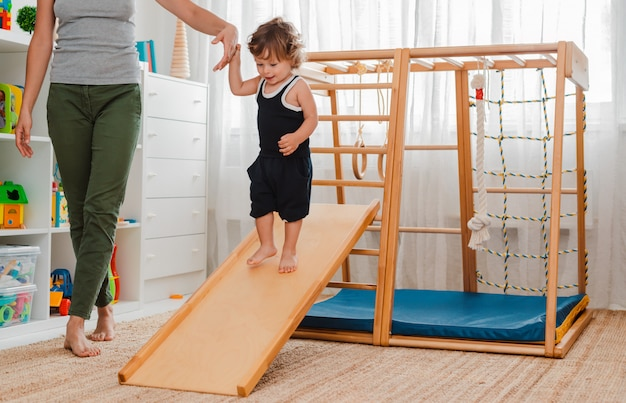 Très jeune, l'enfant est engagé dans le complexe sportif en bois pour enfants de la maison. Photo Premium