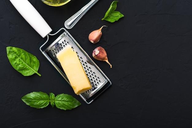 Triangle De Parmesan Sur Râpe, Ail, Basilic Vert. Ingrédients Alimentaires Pour Faire Des Pâtes, Spaghetti, Bruschetta, Pizza, Fettuccine, Sauce Pesto .vue De Dessus, Espace Copie, Fond De Ciment Noir Photo Premium