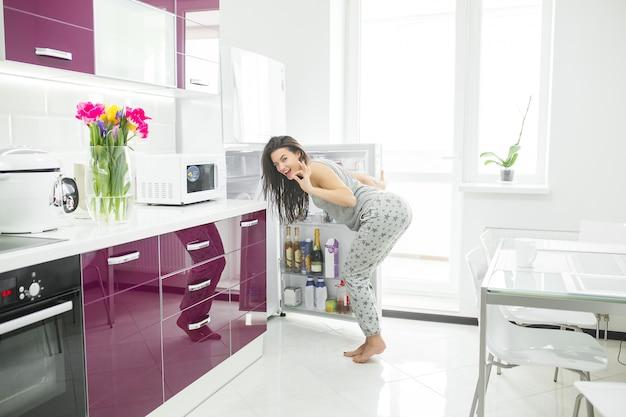 Tricheur De Régime. Femme Sur La Cuisine Près Du Frigo. La Femme Veut Manger. Dame Affamée Le Matin. Photo Premium