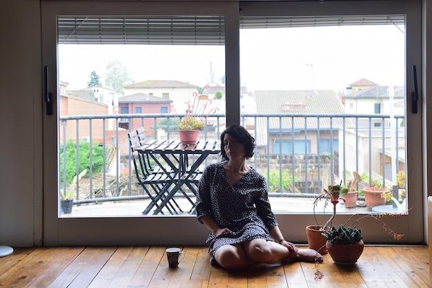 Triste femme assise et regardant par la fenêtre Photo Premium