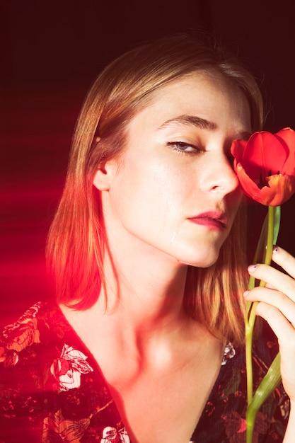 Triste femme blonde avec une tulipe rouge Photo gratuit