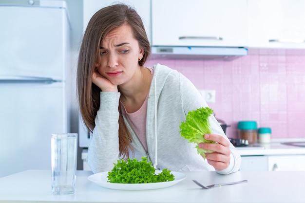 Triste femme malheureuse est fatiguée de suivre un régime et de ne pas vouloir manger des aliments diététiques sains et biologiques Photo Premium