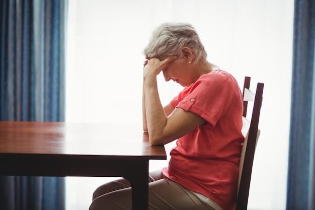 Triste Femme Senior Assise à Une Table Photo Premium
