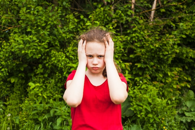 Triste fillette ayant mal à la tête en regardant la caméra debout dans le parc Photo gratuit
