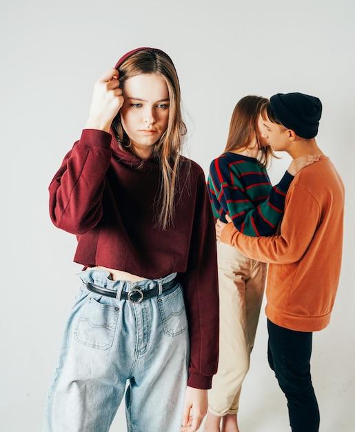 Triste jeune adolescente sur fond de couple d'amoureux, isolé. th Photo Premium