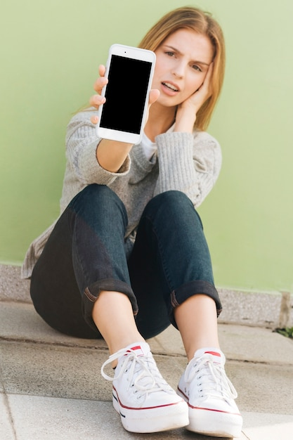Triste jeune femme assise contre le mur vert montrant un téléphone portable Photo gratuit