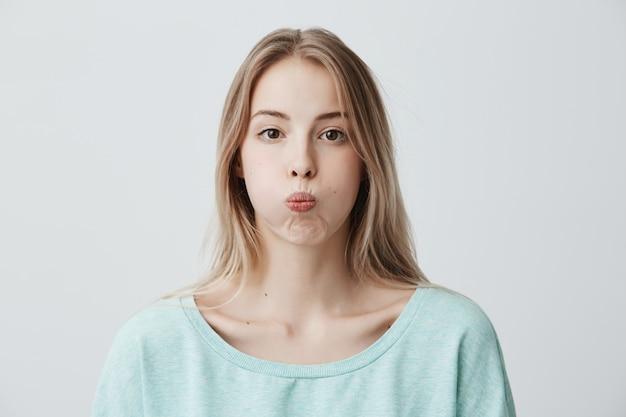 Triste Jeune Femme Blonde A Une Expression Grincheuse Fait La Moue Photo gratuit