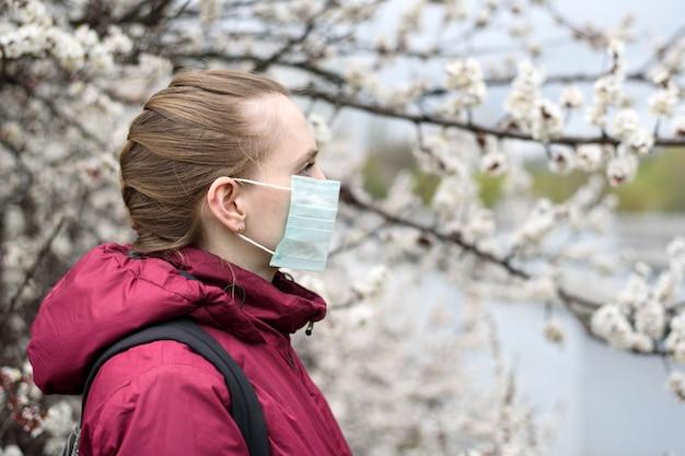 Triste jeune femme en masque de protection médical. arbre en fleurs sur. allergie de printemps. Photo Premium