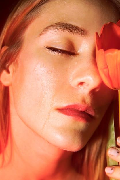 Triste jeune femme avec une tulipe rouge Photo gratuit