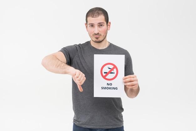 Triste jeune homme ne tenant aucun signe de fumer montrant le pouce vers le bas de geste sur fond blanc Photo gratuit