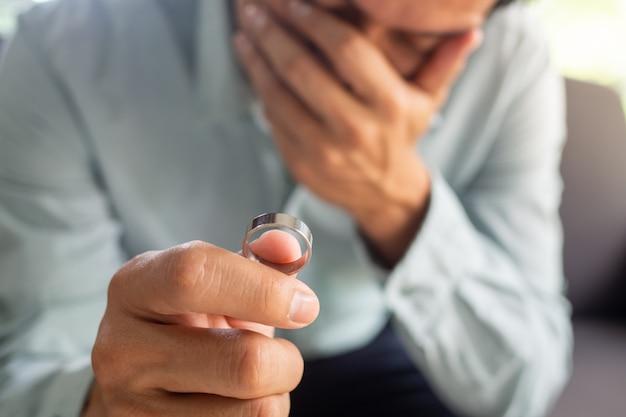 Le Triste Mari Après Le Divorce Tient La Bague De Mariage. La Fin Des Problèmes Familiaux Photo Premium