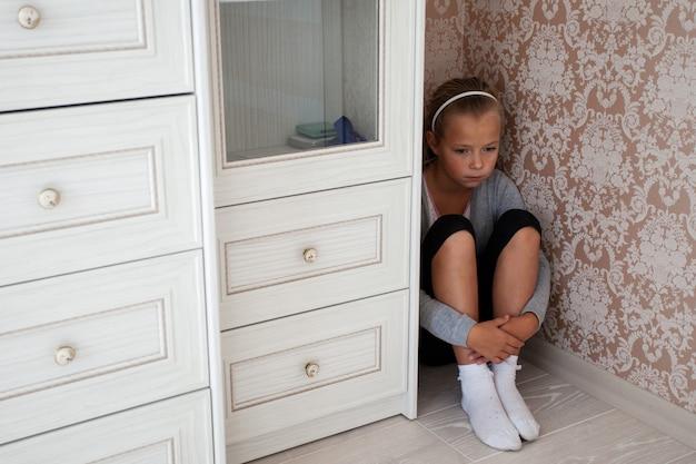 Triste petite fille assise dans le coin d'une pièce Photo Premium