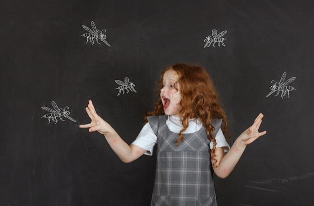 Triste petite fille peur des piqûres de moustiques qui volent autour d'elle. Photo Premium