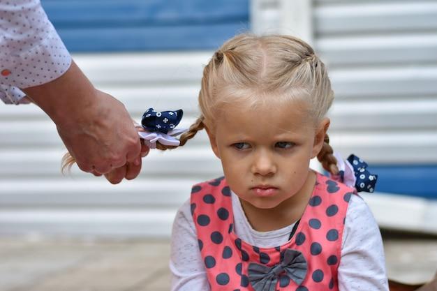 Triste petite fille s'assoit et attend pendant que maman tresse ses cheveux de ses cheveux Photo Premium