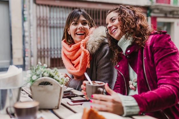 Trois amies prenant un café sur une terrasse à porto, au portugal. avoir une conversation amusante Photo Premium
