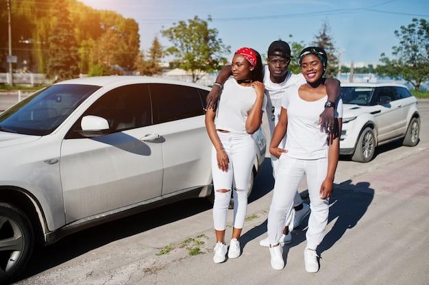 Trois Amis Afro-américains élégants, Portent Des Vêtements Blancs Contre Deux Voitures De Luxe. Mode De Rue Des Jeunes Noirs. Homme Noir Avec Deux Filles Africaines. Photo Premium