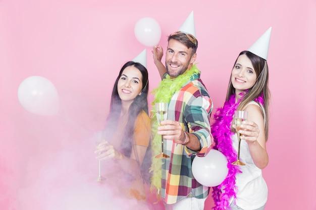 Trois Amis Appréciant La Flûte De Champagne Dans La Fête Photo gratuit