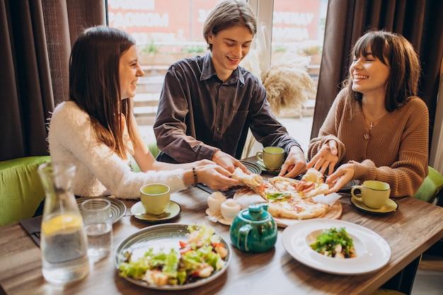 Trois Amis Ensemble Manger De La Pizza Dans Un Café Photo gratuit
