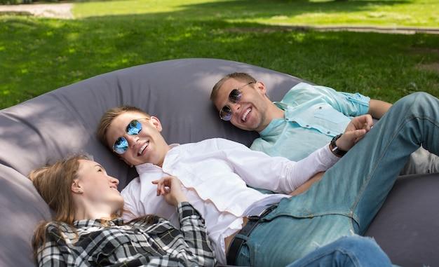 Trois amis qui rient heureux se détendre en plein air dans le parc sur un grand coussin d'oreiller. Photo Premium