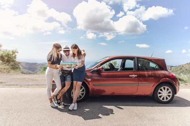 Trois amis en regardant la carte debout près de la voiture moderne sur la route Photo gratuit