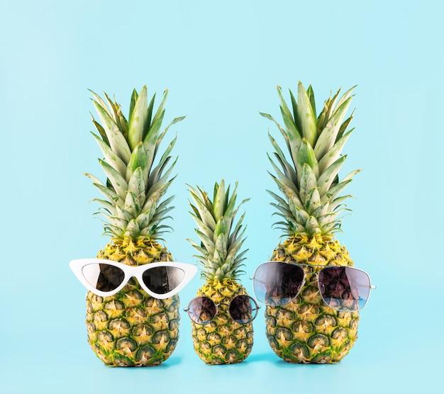Trois ananas avec des lunettes sous la forme d'une famille de trois personnes en vacances. concept de voyage d'été dans les pays tropicaux Photo Premium