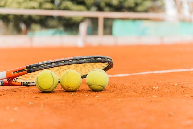 Trois balles de tennis avec raquette Photo gratuit