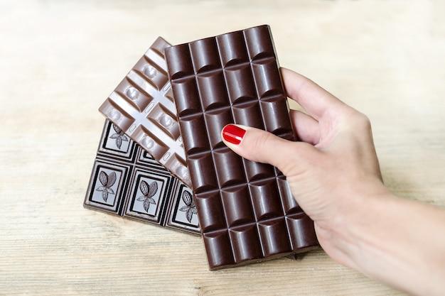 Trois barres de chocolat de différents types dans une main féminine Photo Premium
