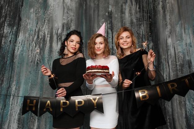 Trois belles filles célèbrent leur anniversaire en tenant un gâteau et des feux de bengale Photo gratuit