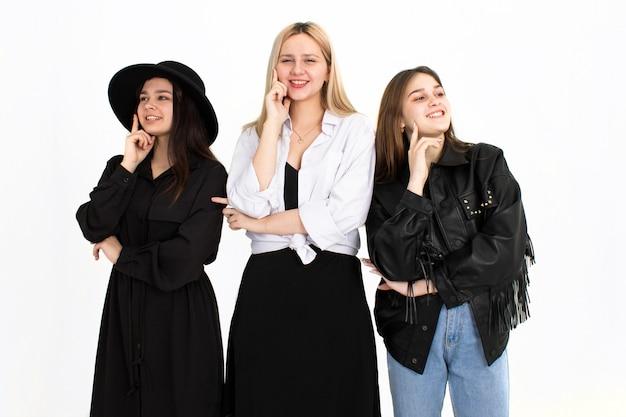 Trois Belles Jeunes Filles Envisagent De Résoudre Le Problème. Photo Sur Fond Blanc Photo Premium
