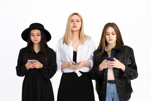 Trois Belles Jeunes Filles Regardent Leurs Smartphones. Photo Sur Fond Blanc Photo Premium