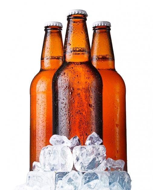 Trois bouteilles de bière brune avec de la glace isolé Photo Premium