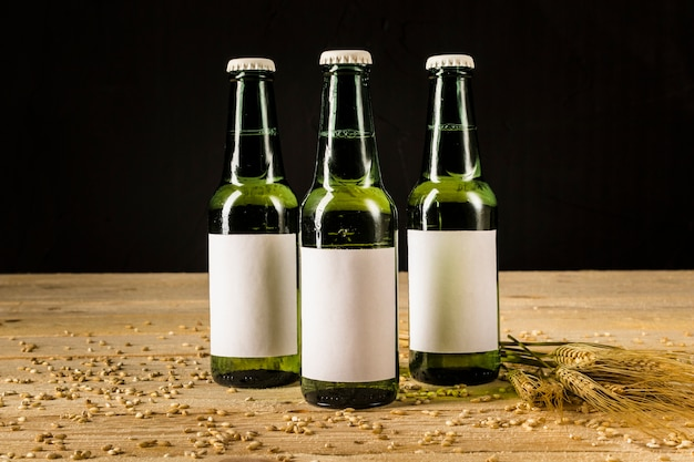 Trois bouteilles de bière verte avec des épis de blé sur une surface en bois Photo gratuit