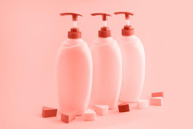 Trois bouteilles en plastique avec distributeur sur fond corail. Photo Premium