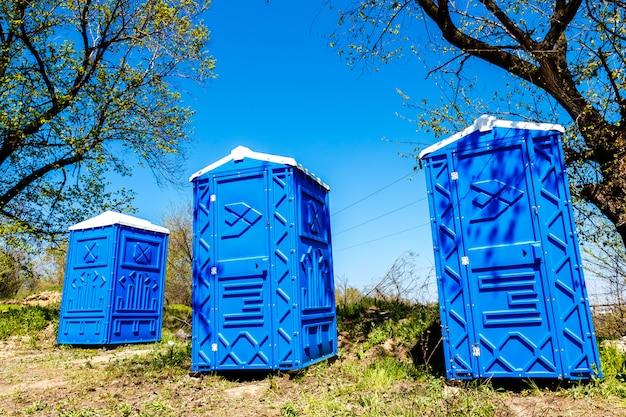Trois cabines bleues de toilettes chimiques dans un parc à la journée d'été ensoleillée. Photo Premium